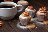 Cupcake with nuts and caramel on old wooden table