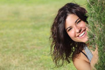 Beautiful woman peeking through a tree and smiling