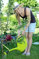 Junge Frau gießt Blumen im Garten mit Gießkanne