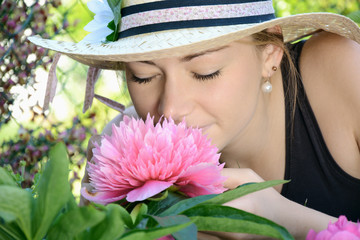 Junge Frau riecht an Rhododendron-Blüte im Garten