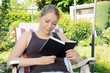 Junge Frau liest Buch im Garten