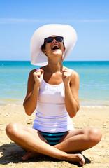 Ragazza che ride seduta sulla spiaggia con sfondo di mare