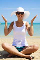 Ragazza allegra seduta sulla spiaggia
