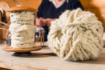 Gesponnene Schafwolle auf Spule und als Ball