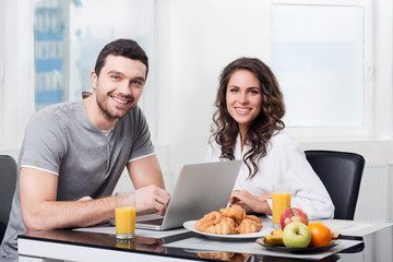 beautiful couple having breakfast with a laptop