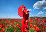 Woman in red clothes with chinese umbrella posing in poppy field
