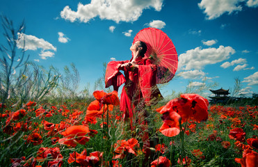 Woman in red clothes with chinese umbrella in the poppy field