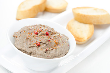 liver pate with pink pepper in a white bowl and toasted bread