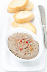 liver pate with pink pepper in a white bowl, top view