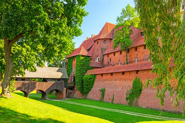 he wall and towers of Malbork castle in summer scenery, Poland