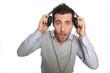 Portrait of astonished guy taking headphones off