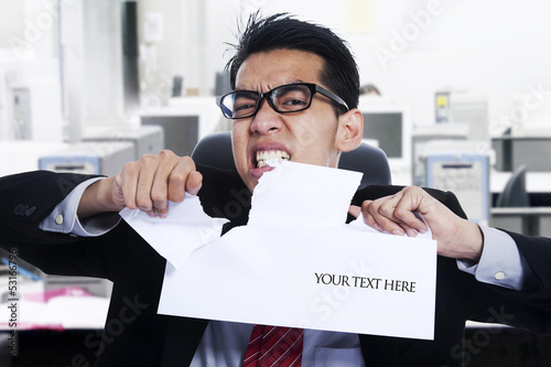 Angry businessman tear paper at office