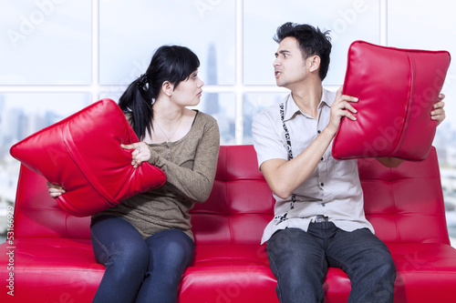 Angry couple on red sofa at apartment