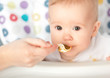 Mother feeds funny baby from  spoon