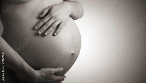 Leinwanddruck Bild belly of pregnant woman  monochrome on dark background