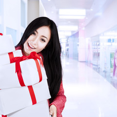 Attractive female shopper bring boxes at mall