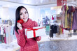 Attractive woman show gift card and present in shopping mall
