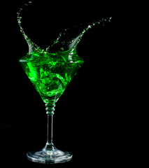 blue cocktail splashing into glass on black