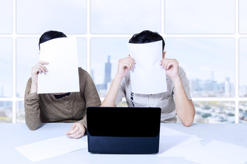 Couple hiding behind papers sitting with laptop