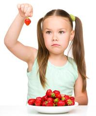 Little girl is eating strawberries