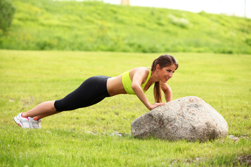 Beautiful young woman working out near stone