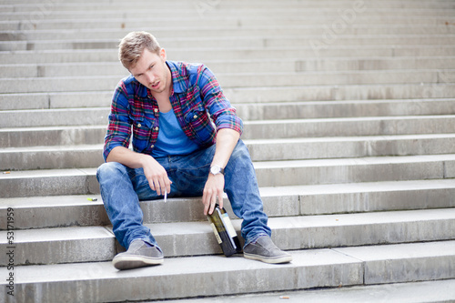 Drunk man sitting on the stairs drinking wine and smoking cigare