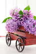 Purple lilac flower bouquet in a wooden carriage