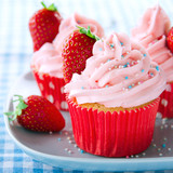 Pink cupcakes with fresh strawberries and sprinkles