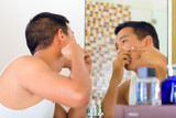Asian man discovering a pimple in face poster