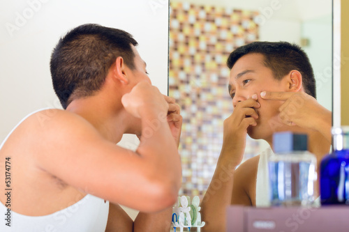Asian man discovering a pimple in face