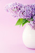 White vase with a bouquet of lilacs