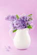 White vase with a bouquet of purple lilac flowers
