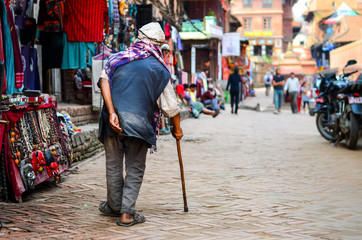 Poor old man walking with stick in exotic asian street