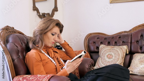 Lady reading a book on a sofa, bored