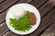 Cutlet dinner with rice and green peas