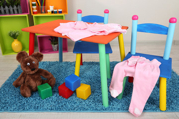 Small and colorful table and chairs with baby clothes