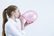 Girl blowing up pink balloon