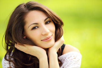 Image of young beautiful woman in summer park smiling