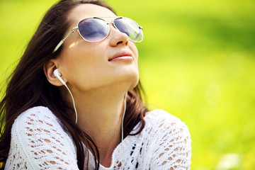 Image of young beautiful woman in summer park enjoy music