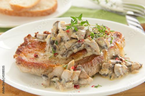 Pork steak with mushroom sauce and cream.