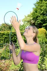 Junge Frau spielt Badminton im Park