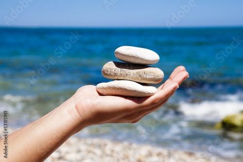 Papiers peints Zen pierres a sable Rocce nella mano con sfondo di mare
