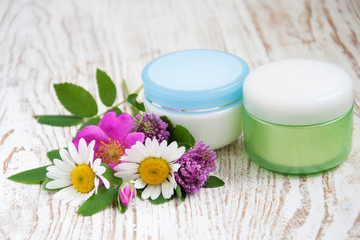 containers with cream  and wild flowers