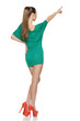 Back view of female in green dress in full length pointing up