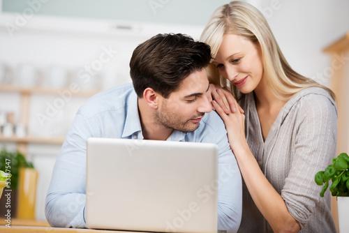 junges paar mit laptop in der küche