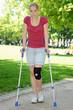 Junge Frau mit Kniebandage geht an Krücken