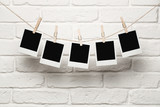 Blank photos hanging on a clothesline over brick wall background