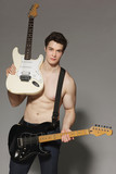 Muscular man with bare torso handing two electric guitars