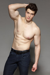 Sexy young man with bare torso with hand on his head
