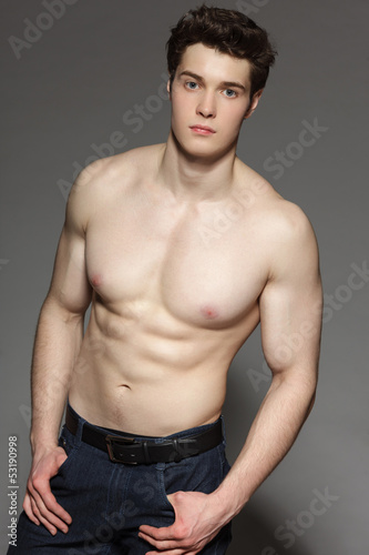 Young man with bare torso stansing with hands in pockets
